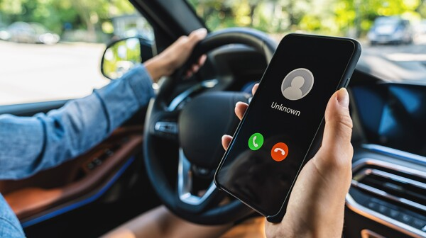 Unknown number calling while car driving. Phone call from stranger. Person holding mobile and smartphone in livingroom late. Unexpected call disturbs at car ride.