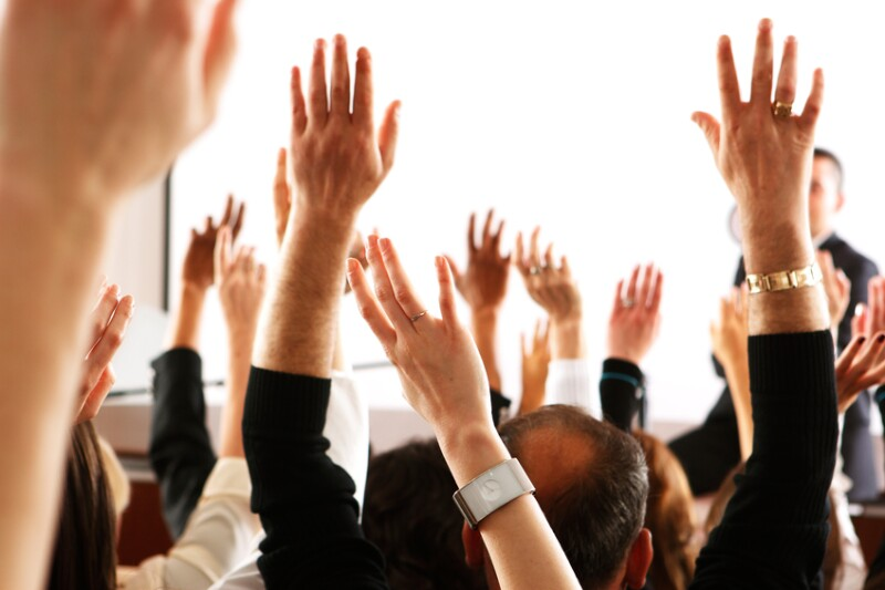 Voting audience, business spectators or students raising hands in seminar