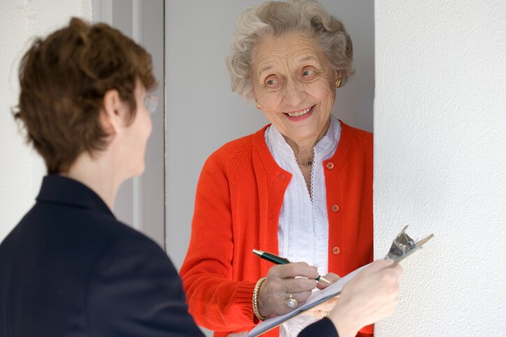 Smiling senior woman signing petetion