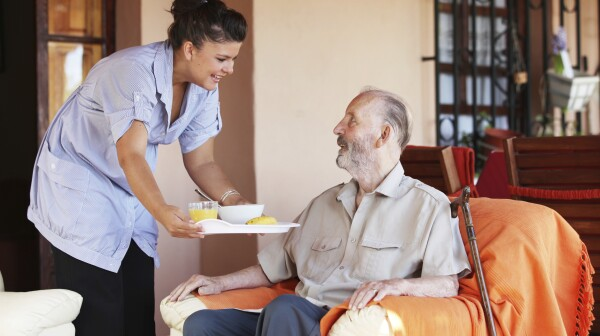 elderly senior being brought meal by carer or nurse