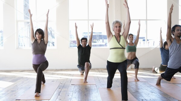 Six adults practicing yoga, arms raised
