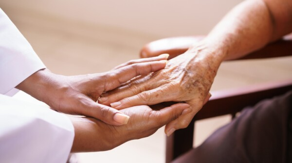 Senior Woman Talking With Black Doctor In Hospice