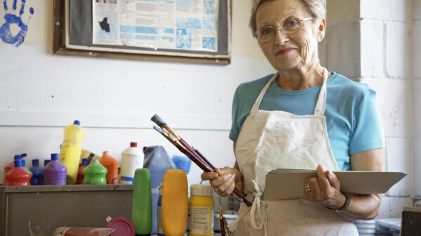 """Mature woman in art classroom, holding brushes and paper, portrait"""