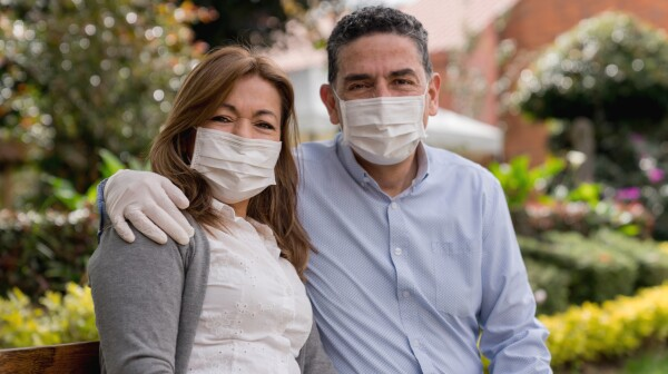 Happy adult couple outdoors wearing facemasks