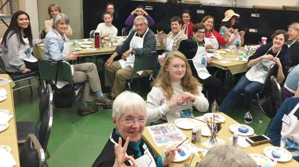 A group of older adults and Girl Scouts painting at tables
