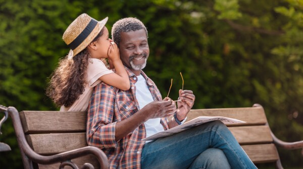 grandchild whispering to her smiling grandfather while sitting on bench in park