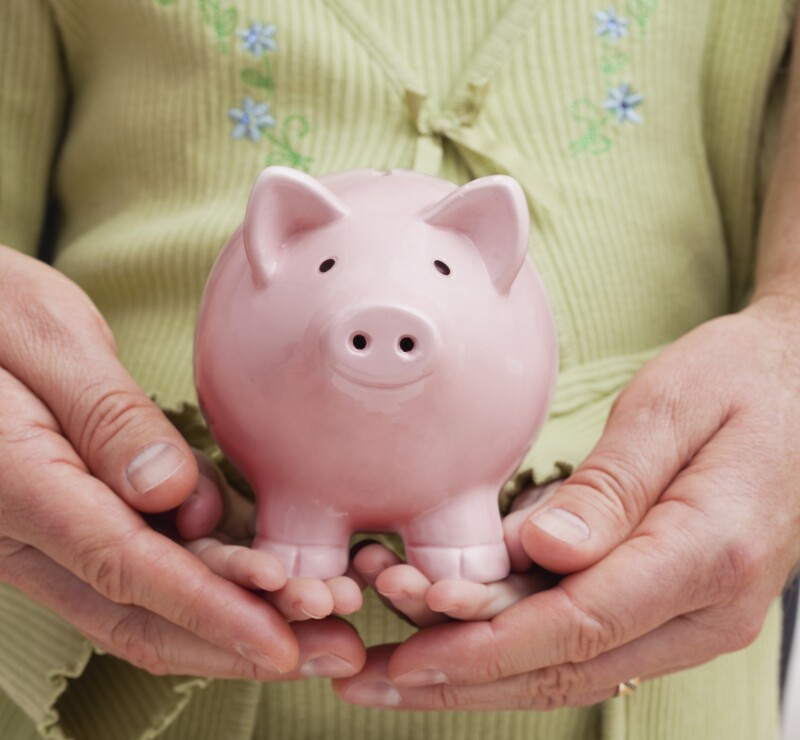 USA, Illinois, Metamora, Close-up of father's and daughter's (6-7) hands holding piggy bank
