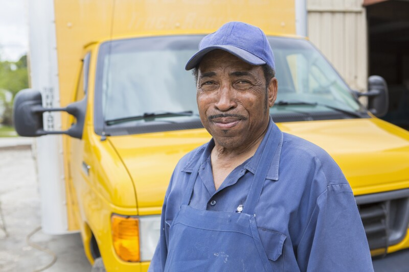 African American worker smiling by truck