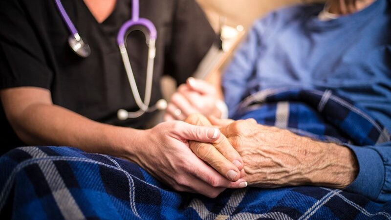 Nursing home staff and resident holding hands