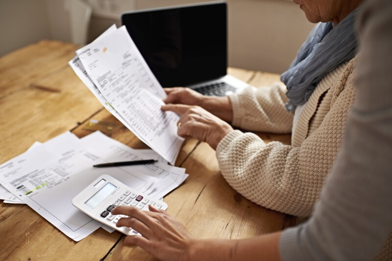 Helping senior pay bills_calculator and papers_©PeopleImages