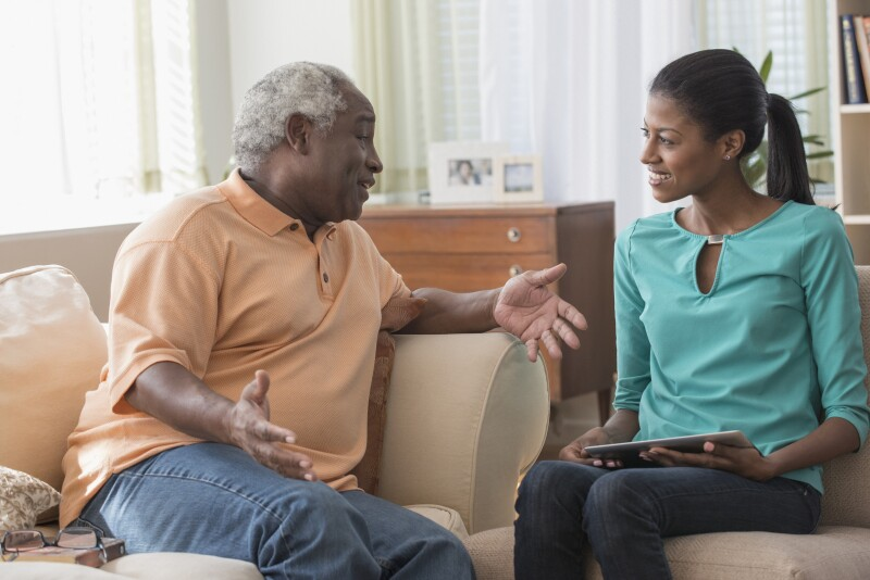 Father and daughter talking on sofa in living room