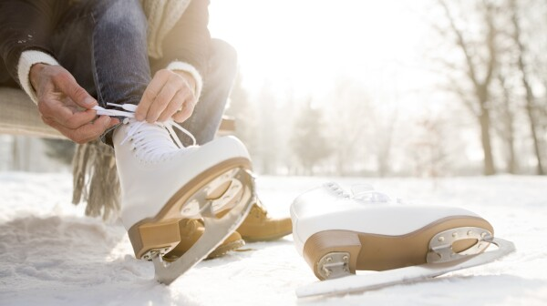 Woman sitting on bench in winter putting on ice skates