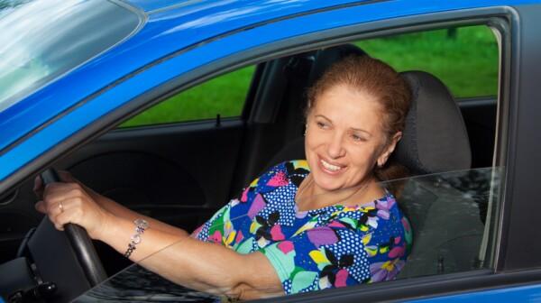cheerful senior woman driving