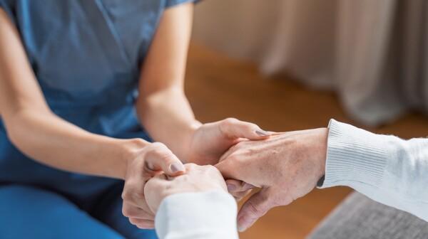 nurse hold hands of a nursing home resident