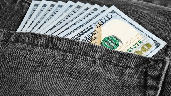 Many greenback in a pocket of jeans
