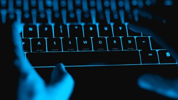 Hacker typing on the illuminated  keyboard by night.