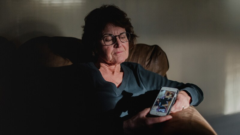 A woman sits in a chair holding a cell phone