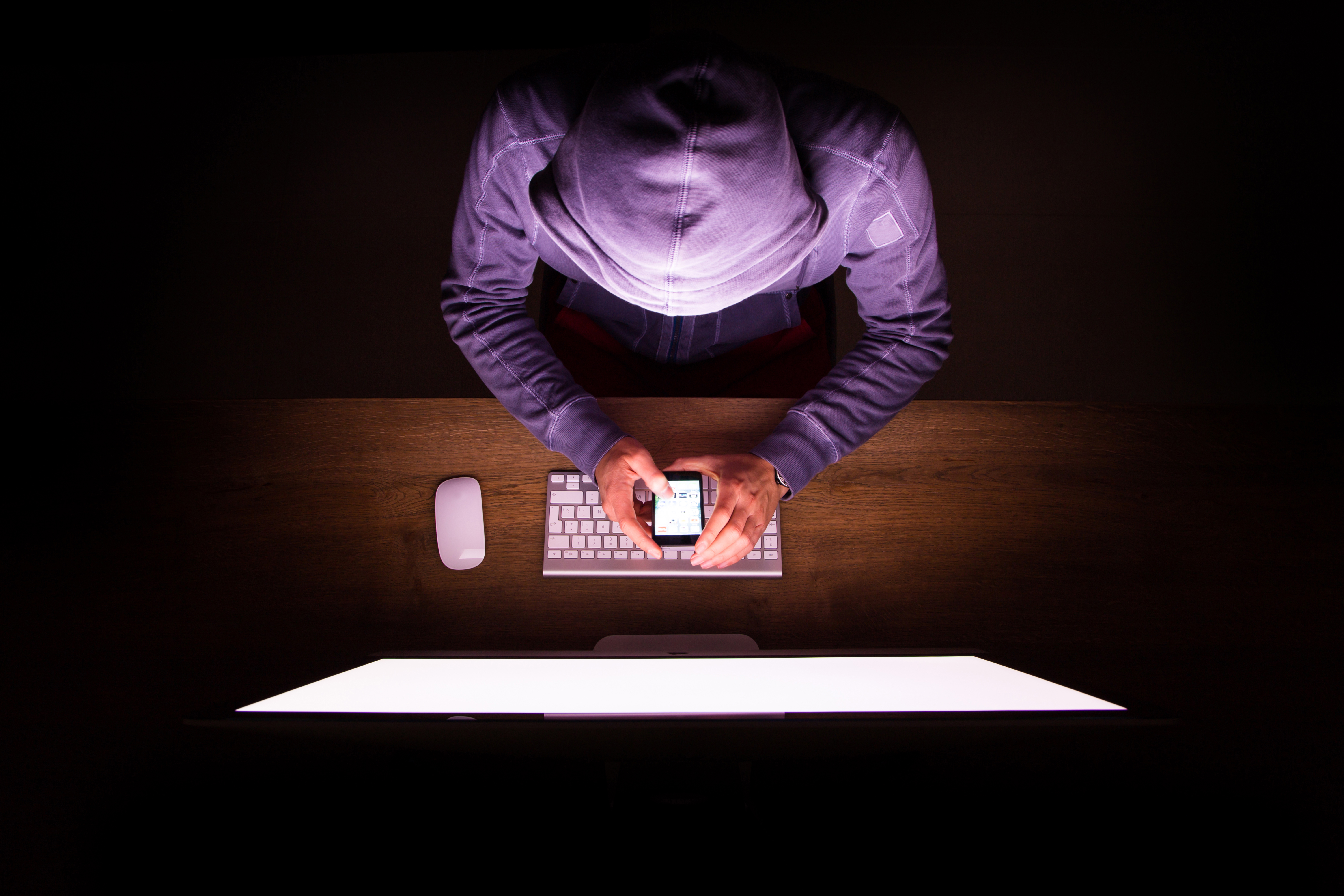 A mysterious scammer hacks into private information through a computer and smart phone.