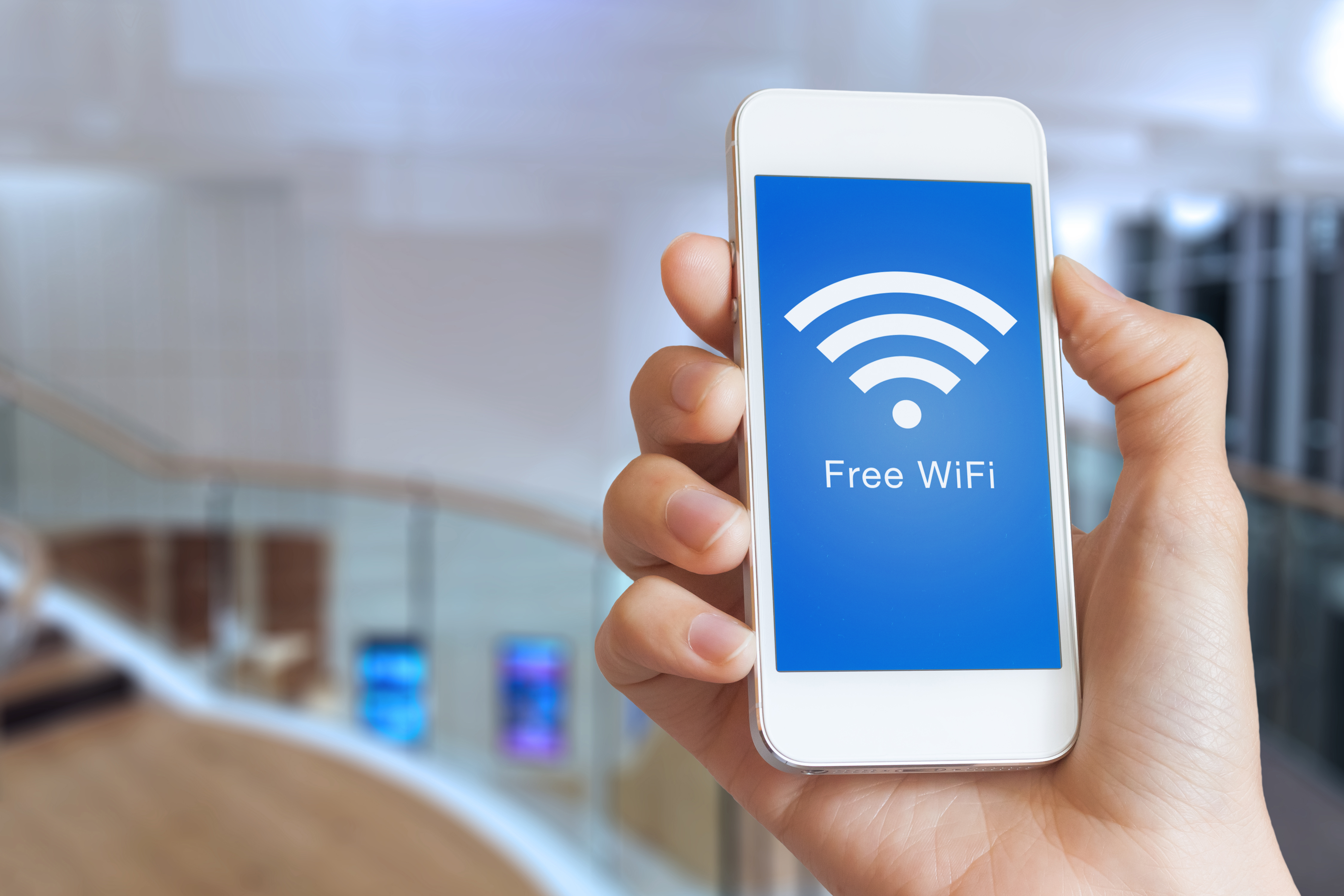 Closeup hand holding smartphone with free WiFi hotspot on screen