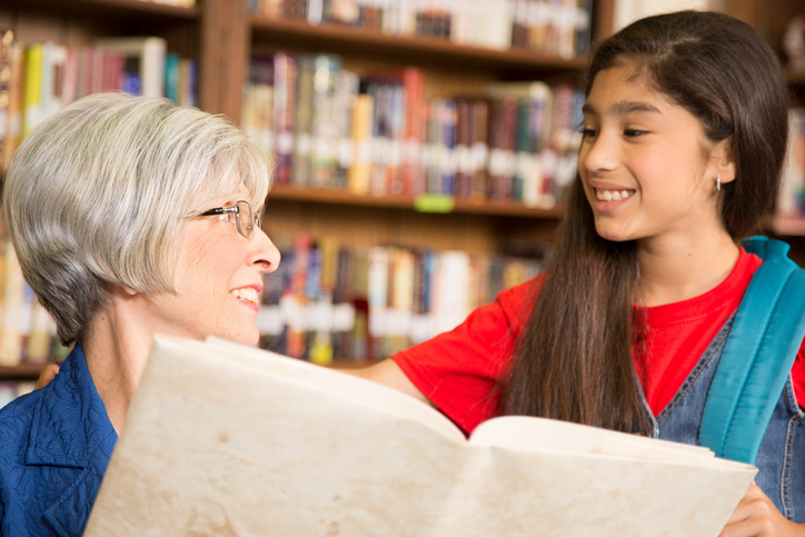 Teacher, librarian reads book to elementary student in library or classroom.
